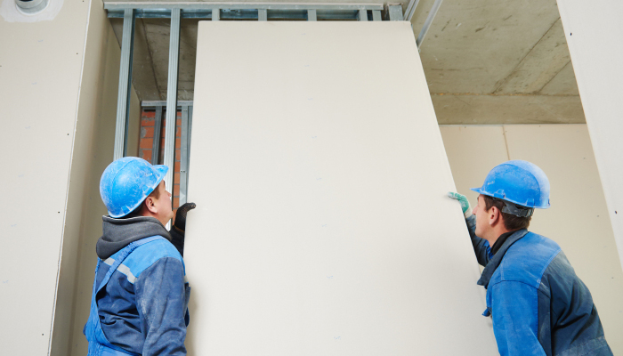 Image shows D & J Plastering completing a dry lining job using tacking